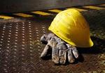 Arbeitshandschuh und Schutzhelm liegen auf Trittblech