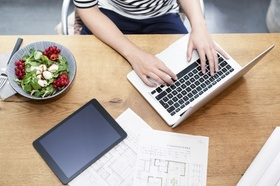 Arbeitsplatz mit Laptop, Tablet und gesundem Salat