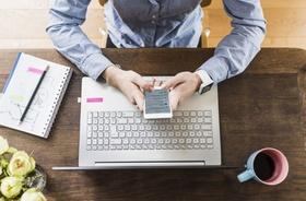 Arbeitsplatz von oben mit Laptop, Smartphone und Notizblock