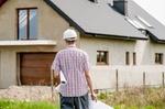 Architekt mit Bauplan unter dem Arm vor Haus