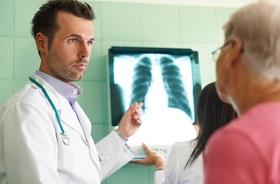 Arzt bespricht Röntgenbild mit Patienten