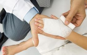 Arzt legt kleinem Kind Verband an Hand an