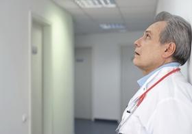 Arzt mit Stethoskop um den Hals lehnt an einer Wand im Flur