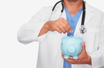 Arzt mit Stethoskop um den Hals und Sparschwein in der Hand