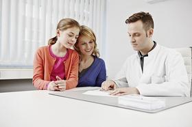 Arzt sitzt mit einer Frau und einem Kind am Schreibtisch