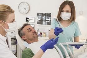 Arzthelferin gibt Zahnärztin eine Spritze Patient liegt auf Stuhl