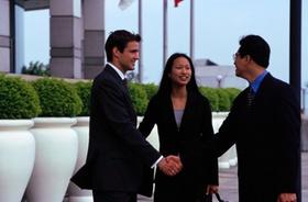 asiatische Frau + Mann schütteln Hände mit westlichem Mann