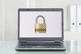 Aufgeklappter Laptop mit Sicherheitsschloss auf Monitor