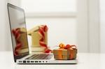 Aufgeklapptes Laptop auf dem ein Geschenk steht