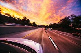 Auto fährt dem Sonnenuntergang entgegen