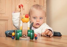 Baby sitzt mit Spielzeug am Tisch