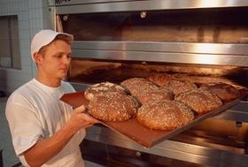 Bäcker mit Broten vor Ofen