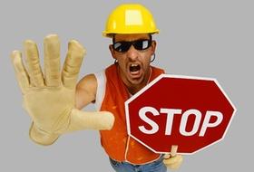 Bauarbeiter der ein Stopschild in der Hand hält
