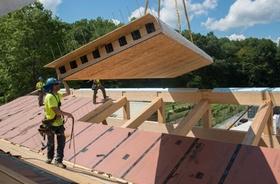 Bauarbeiter heben fertiges Dachbauteil aufs Dach