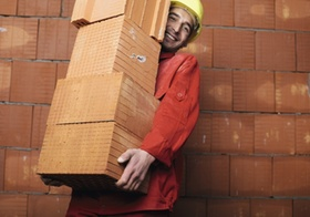 Bauarbeiter schleppt Ziegelstapel