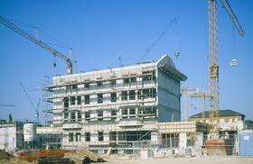 Baustelle von Mehrfamilienhaus mit Gerüst und 2 Kränen
