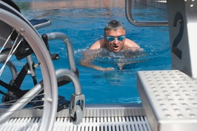 Behindertensport, Mann schwimmt im Schwimmbecken, Rollstuhl steht am Rand