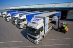 Worker driving forklift loading semi-truck on loading dock
