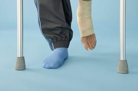 Bildausschnitt zwei Krückenenden plus zwei Beine, davon eines bandagiert