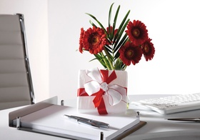 Blumenstrauss und Geschenkpaeckchen auf Schreibtisch