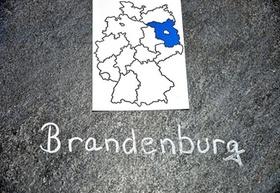 Brandenburg-Karte und Schriftzug mit Kreide auf Straße