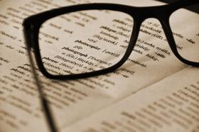 Brille liegt auf Wörterbuch