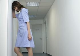 Brünette Frau in einem Klinikhemd auf dem Flur