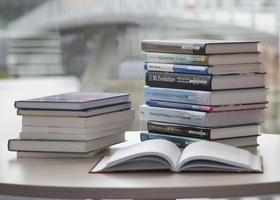 Bücher stapeln sich, ein Buch ist aufgeschlagen