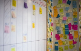 Bunte Notizzettel die an einer Wand und Whiteboard kleben