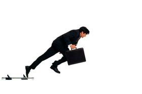 Business-Mann mit Koffer an Sprint-Startblöcken
