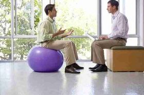 Businessman on exercise ball in meeting with colleague using laptop computer in exercise studio, sid