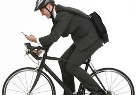 Businessmann auf Rennrad mit Handy