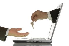 Businessmann reicht anderem Mann mit Hand aus Computer einen Schlüssel