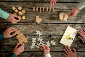 Businessmen planning business strategy while holding puzzle pieces, creating ideas with light bulb d