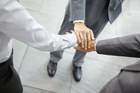 Closeup of group of business people with hands together
