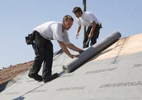 Dachdecker rollen Dachpappe auf Dach aus