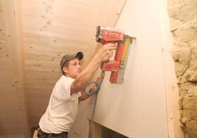 Handwerker befestigt mit Tacker Daemmmaterial bei Hausbau