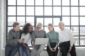 Divers zusammengestelltes Team schaut gemeinsam in einen Laptop