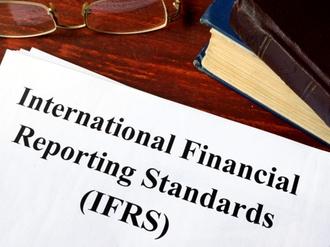 Dokument International Financial Reporting Standads auf Tisch mit Brille und Buch