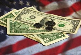 Dollar-Scheine und Münzen auf US-Flagge