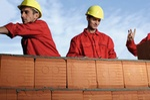 Drei Bauarbeiter hinter Ziegelmauer