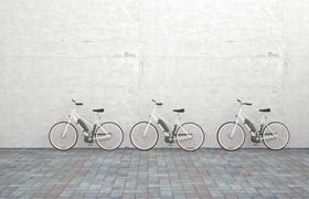 Drei Elektrofahrräder vor Betonwand