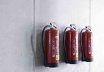 Drei Feuerloescher haengen an Wand