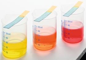 Drei Glasbecher mit farbigen Fluessigkeiten und Teststreifen