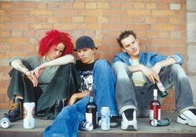 Drei Jugendliche sitzen depressiv mit Alkohol am Boden