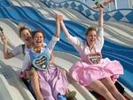 Drei junge Frauen auf Rutsche, Oktoberfest