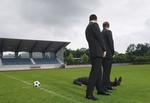 Drei Manager auf Fussballplatz, einer liegt auf Rasen, zwei stehen daneben