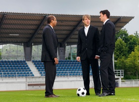 Drei Manager stehen auf Fussballplatz