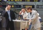 Drei Manager stehen mit Notebooks im Flughafen, telefonieren mit Handys