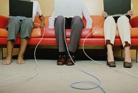 Drei Personen auf Sofa mit Laptop